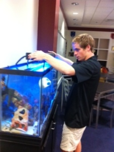 President Andrew cares for the fish tank in the commons