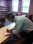 Mr. Gray autographs his book for faculty.