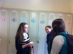 Senior girls chat by their monogrammed lockers.