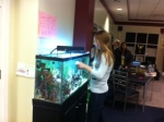 Senior Nicki helps maintain the fish tank for Nemo.
