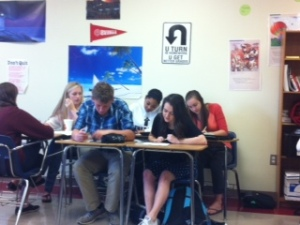 Group work to get to the bottom of assigned reading in English class.