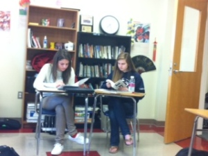 Students work together to pull apart Brave New World.