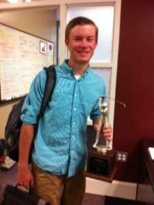Tim, golf team member,  holds trophy.