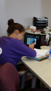 Victoria is listening and watching  Mr. Herder lecture on her laptop. How cool! way to flip the classroom!