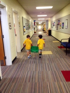 Super cute lower school boys transporting books to the library.