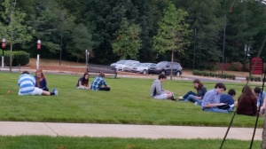 Actors and actresses gather on the front lawn to prep lines.